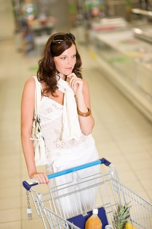 Grocery store - thoughtful woman shopping with troley in supermarket photo