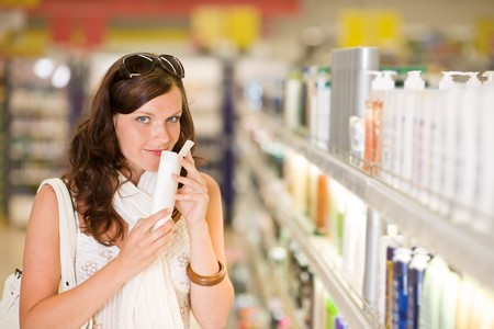 supermarkets: Shopping cosmetics - woman smelling bottle of shampoo in drug-store