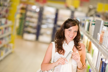 Shopping - smiling woman holding moisturizer in supermarket photo