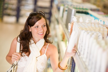 Shopping - smiling woman looking at bottle of shampoo in supermarket photo