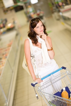Grocery store - thoughtful woman shopping with trolley in supermarket photo