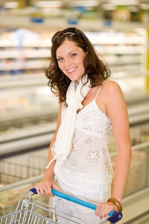 Grocery store - smiling woman shopping with trolley in supermarket photo