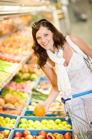 grocery cart: Grocery store - smiling woman shopping with trolley in supermarket, holding orange Stock Photo