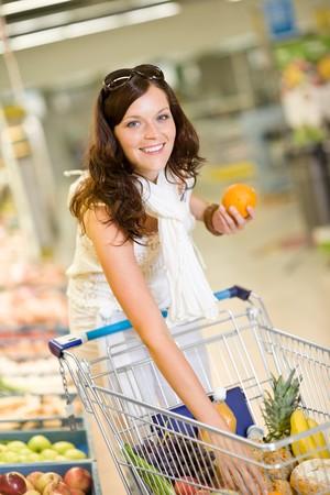 groceries: Tienda de abarrotes - sonriente a mujer de compras con carrito de supermercado, celebraci�n de naranja  Foto de archivo