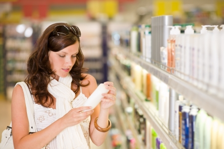 Shopping - young woman holding bottle of shampoo in supermarket Stock Photo - 7218826