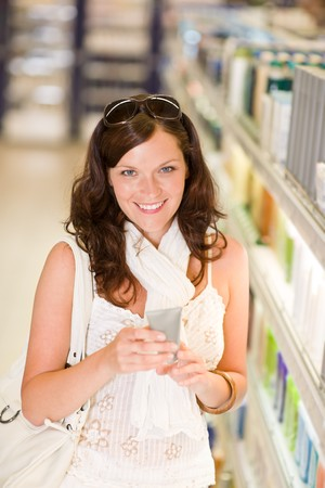 Shopping - smiling woman holding moisturizer in supermarket photo