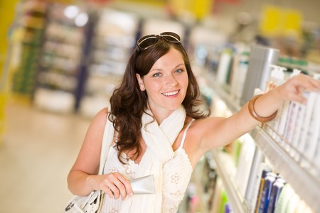Shopping - smiling woman choosing moisturizer in supermarket photo