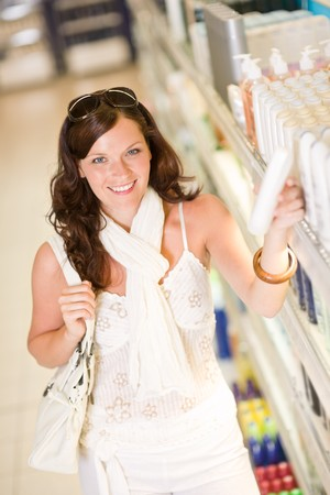 Shopping - smiling woman with bottle of shampoo in supermarket photo