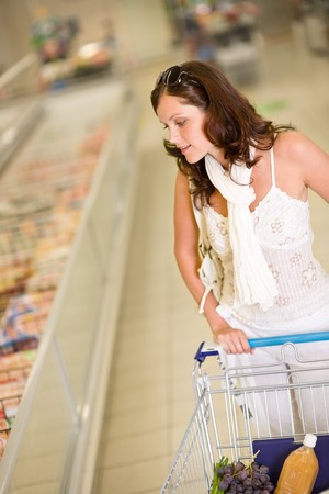 Grocery store - young woman shopping with trolley in supermarket photo