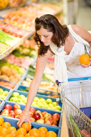 Grocery store - smiling woman shopping with trolley in supermarket, holding orange photo