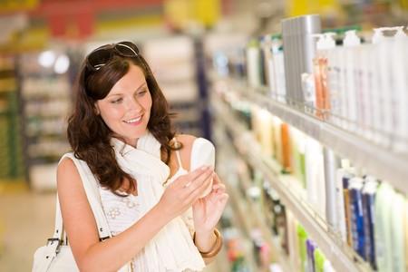 Compras - sonriente a mujer con botella de champú en el supermercado