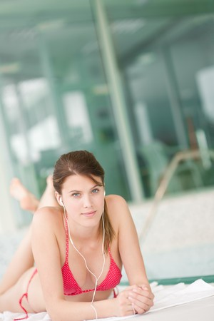 swimming pool woman: Swimming pool - woman relax listen to music with ear buds