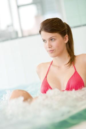 Swimming pool - beautiful woman wearing bikini,  relax in bubble bath photo