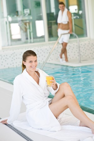 Young woman wearing bathrobe relax at swimming pool, drink juice photo