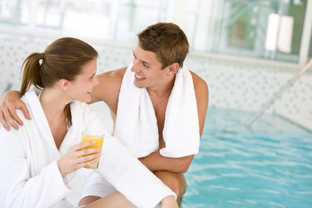 indoor: Young happy couple relax at swimming pool, drink juice