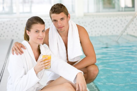 Young sportive couple relax at swimming pool in luxury hotel photo
