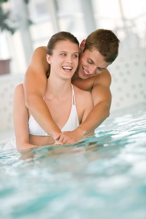 Young sportive couple have fun in swimming pool in luxury hotel Stock Photo - 7324057