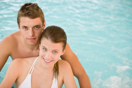 Young sportive couple relax in pool in luxury spa photo