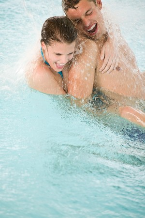 indoor: Young happy couple have fun under water stream in swimming pool