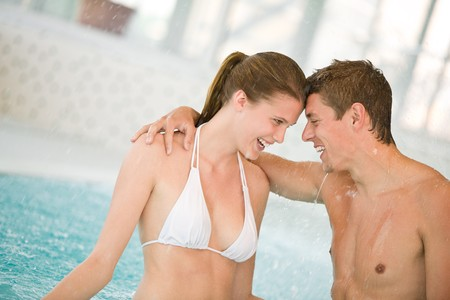 Swimming pool - young loving couple have fun in water photo