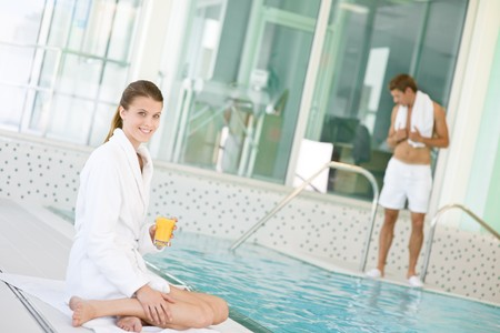 Swimming pool - young woman relax on poolside, hold orange juice photo