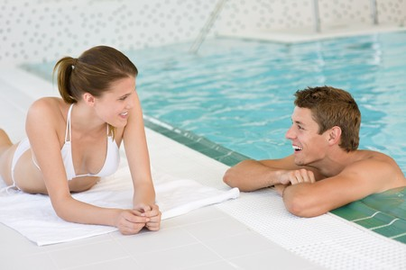 Swimming pool - young happy couple relax on poolside photo