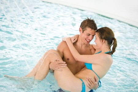 Swimming pool - young loving couple have fun under water stream photo