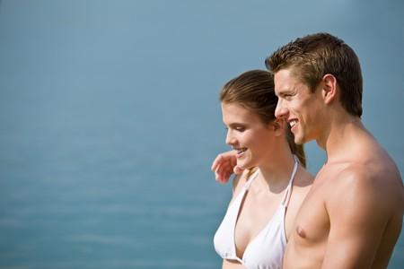 Couple in swimwear enjoy water and sun in summer, standing in sea photo