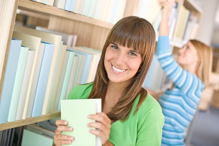 Student in library - two woman choose book from bookshelf