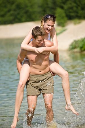 Piggyback - happy couple enjoy sun in nature wearing swimwear photo
