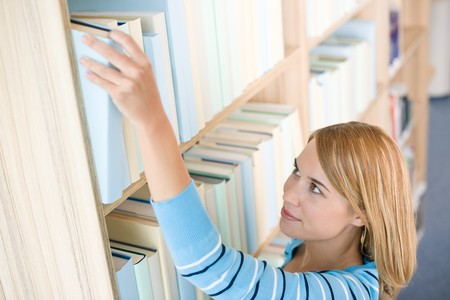 Student in library - happy woman reach for book from bookshelf photo
