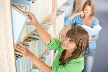Student in library - two happy woman choose book from bookshelf photo