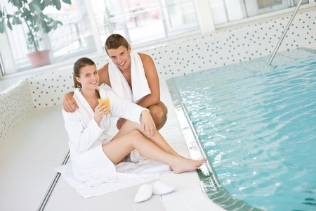Swimming pool - young happy couple relax on poolside in luxury hotel photo