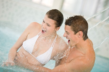 Swimming pool - young couple have fun under water stream on honeymoon photo