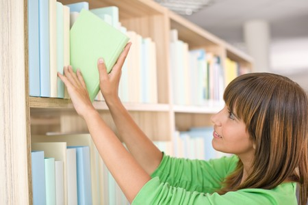 Student in library - happy woman choose book from bookshelf