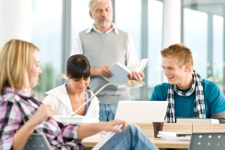 High school - three students with mature professor in classroom Stock Photo - 7825857