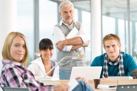 High school - three students with mature professor in classroom Stock Photo - 7825858