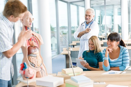 medical school: University - medical students with professor and human anatomical model in classroom