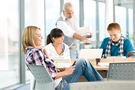 High school - three students with mature professor in classroom Stock Photo - 7835342