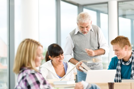 High school - three students with mature professor in classroom Stock Photo - 7835341