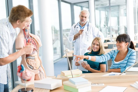 University - medical students with professor and human anatomical model in classroom photo