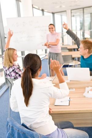 estudiantes de secundaria: Estudiantes de secundaria elevar las manos, en el aula con el profesor  Foto de archivo
