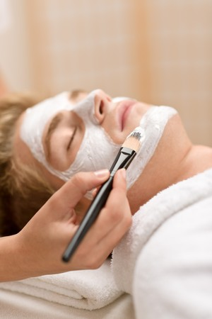 Male beauty - man having facial mask in luxury spa center Stock Photo