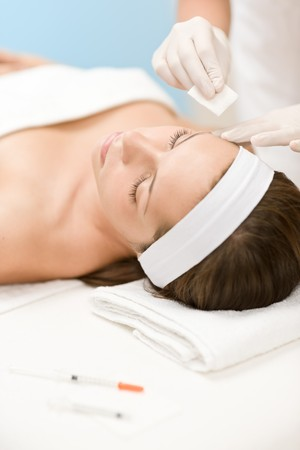 skin treatment: Woman in cosmetic medicine treatment getting botox injection, close-up portrait