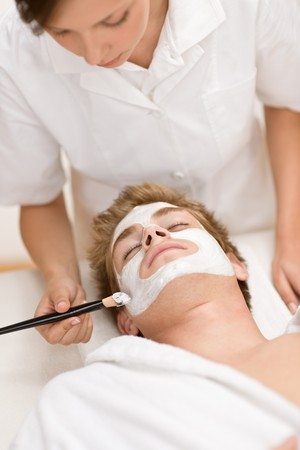 male facial: Male cosmetics - facial mask in luxury spa center Stock Photo