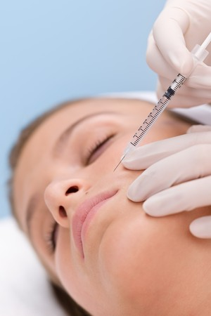 eye patient: Woman in cosmetic medicine treatment getting botox injection, close-up portrait
