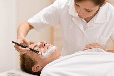 Male cosmetics - facial mask in luxury spa center Stock Photo