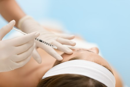 Woman in cosmetic medicine treatment getting botox injection, close-up portrait