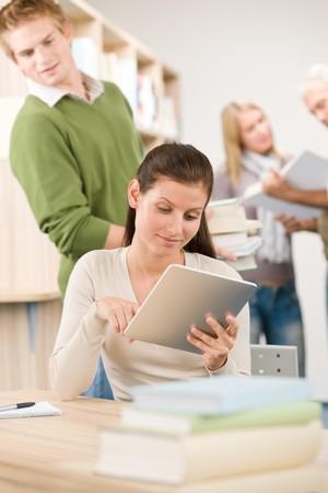 Appuyez sur ordinateur tablette écran - groupe d'étudiants dans la bibliothèque