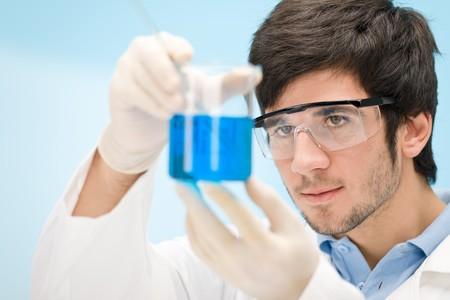 vaso de precipitado: Experimento de qu�mica - cient�fico en laboratorio, gafas protectoras de desgaste  Foto de archivo